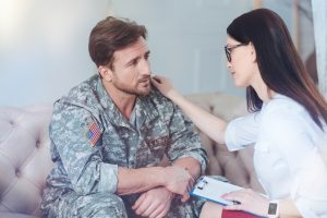 Cheerful female psychologist calming worried soldier